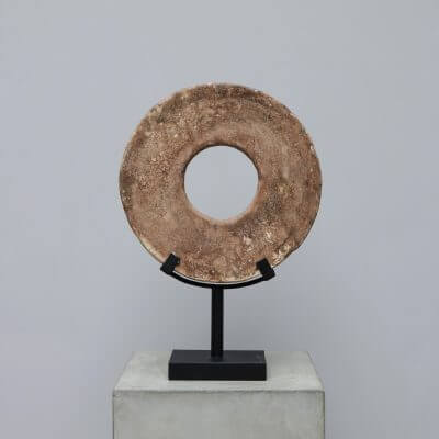 The stone disk is a representation of the currency, Yap, used in the Yap islands of Micronesia.