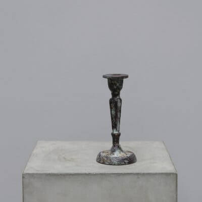Iron candle holder with a patinated finish. Rustic and antique looking design. Scandinavian living with wabi-sabi style
